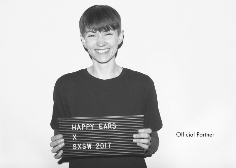 smiling woman with short hair and t shirt holding up a sign that says happy ears X SXSW 2017