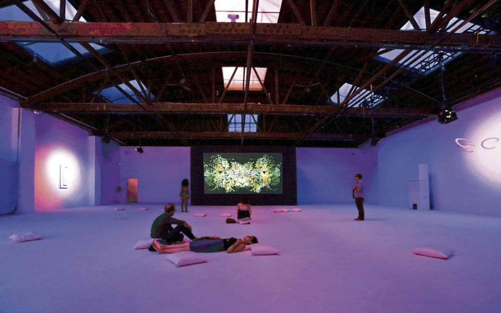 a hangar with pillows scattered on the floor and dim lights on the walls
