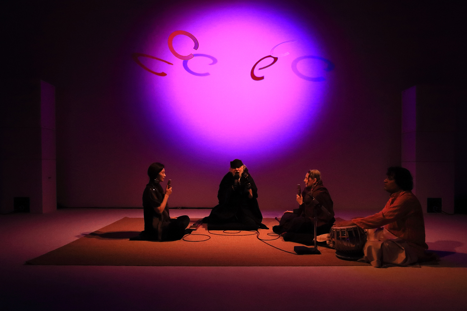 Four people sitting on the floor and singing together